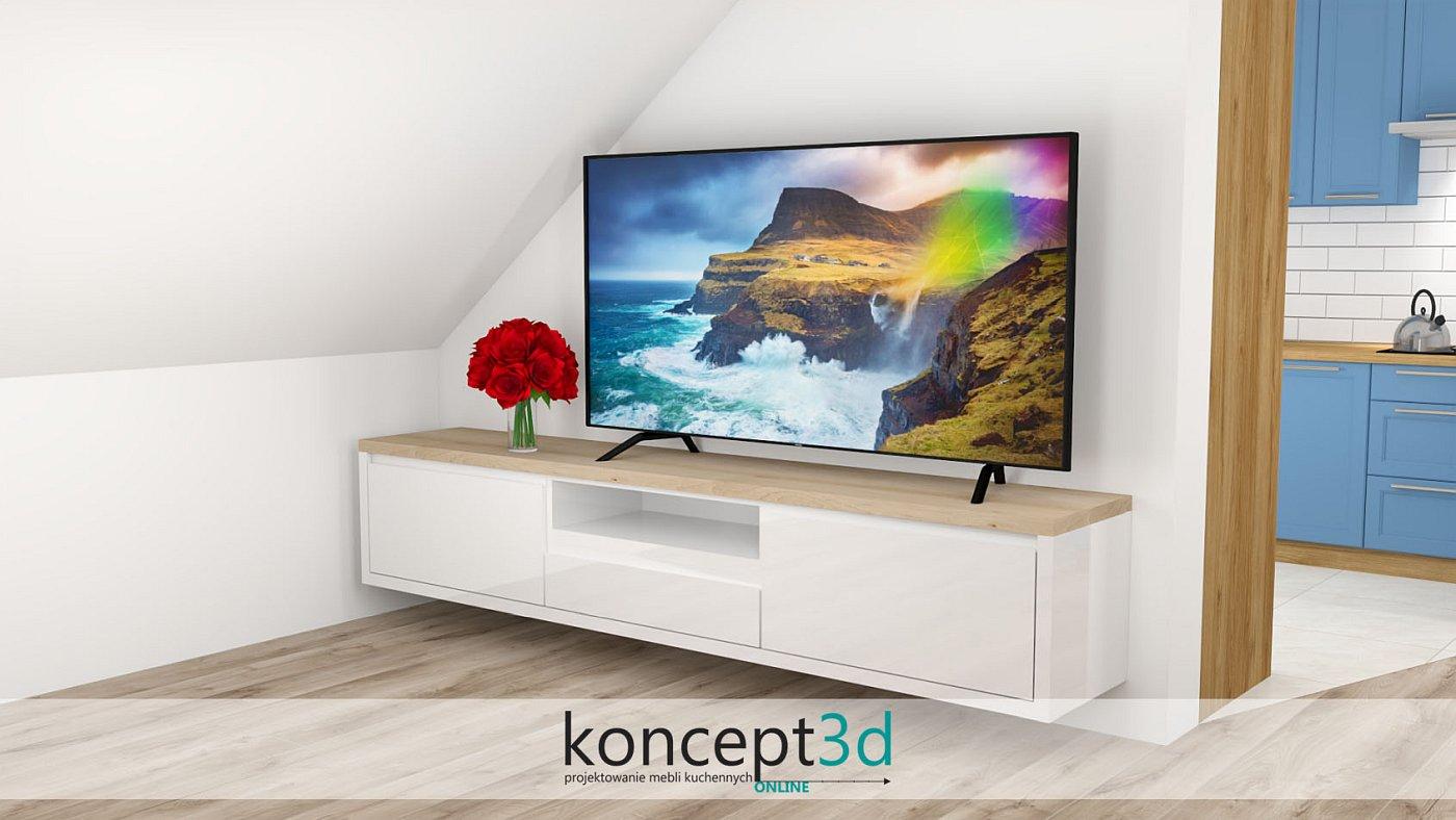 Stojący telewizor i biała szafka RTV. W tle widzimy niebieską kuchnię